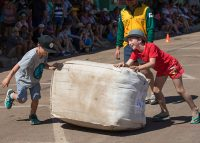 Boys rolling wool bale at Outback Festival