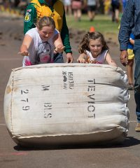 Girls rolling wool bale at Outback Festival 2017