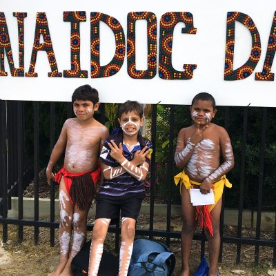 Children leaning on the fence with body paint and traditional dress