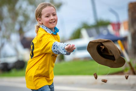 girl in yellow shirt throwing swag hat