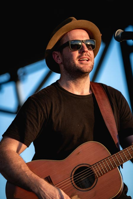 Male musician playing guitar with sunglasses and hat on