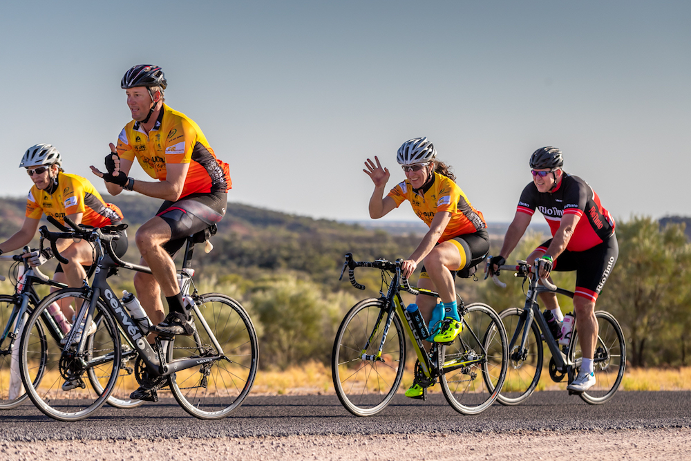 Competitors waving in century cycle comp